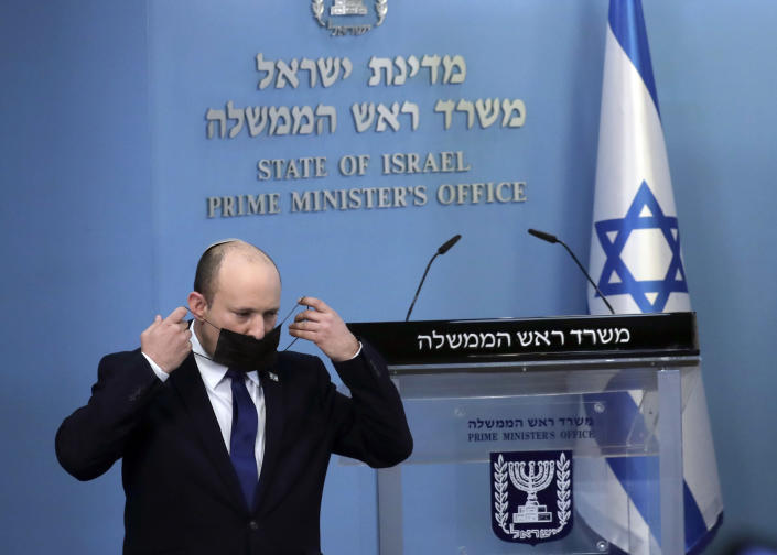 Israel's Prime Minister Naftali Bennett puts on a face mask used as a protective against the coronavirus after delivering a statement in Jerusalem, Wednesday, July 14, 2021. Bennett said Wednesday that Israel can beat a concerning rise in new coronavirus cases without a nationwide shutdown, but he called on people to wear masks indoors and otherwise comply with safety rules. (AP Photo/Maya Alleruzzo)