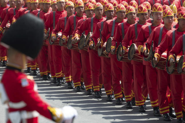 <p>A Thai royal palace honer guard stands in attention as traditional drummers walk in a procession moving late Thai King Bhumibol Adulyadej's ashes to special locations for further Buddhist rites in Bangkok, Thailand Friday, Oct. 27, 2017. With solemn faces and outright tears, Thais said farewell to their king and father figure with elaborate funeral ceremonies that cap a year of mourning and are steeped in centuries of tradition. (Photo: Wason Wanichakorn/AP) </p>