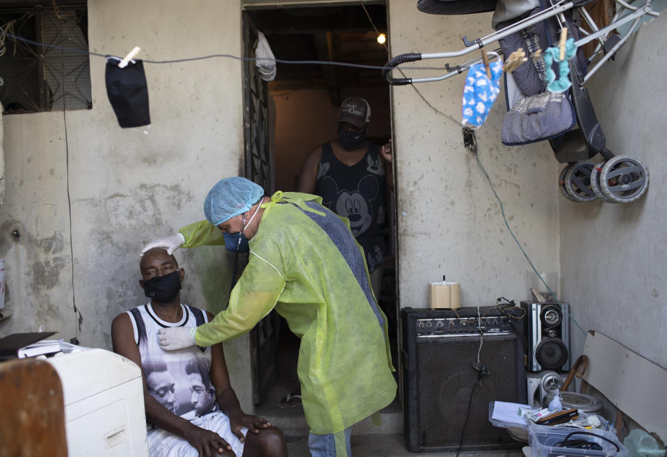Dr. Wille Baracho checks on Mario de Santos, suspected of suffering COVID-19, at his home in the Vila Vintem favela in Rio de Janeiro, Brazil, Tuesday, May 19, 2020. Vila Vintem is home to more than 15,000 people. Its name reflects its undesirable location: when first settled, the swampy area was said to be worth not even a vintem – the cheapest coin at the time, akin to a penny. (AP Photo/Silvia Izquierdo)