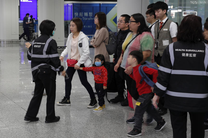 """Health surveillance officer use device to check temperature of passengers before the immigration counters at International airport in Hong Kong, Saturday, Jan. 4, 2020. Hong Kong authorities activated a newly created """"serious response"""" level Saturday as fears spread about a mysterious infectious disease that may have been brought back by visitors to a mainland Chinese city. (AP Photo/Andy Wong)"""