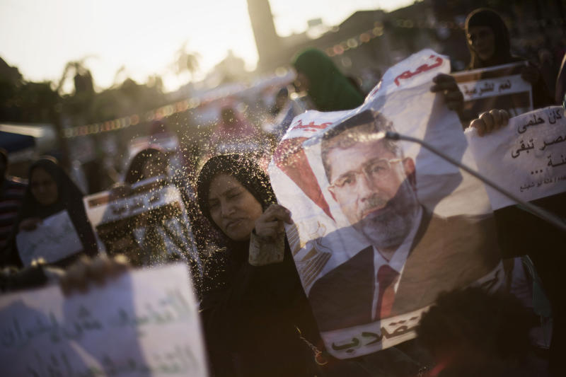 """A supporter of Egypt's ousted President Mohammed Morsi sprays water on an Egyptian woman during a protest near Cairo University in Giza, Egypt, Thursday, August, 1, 2013. Authorities offered """"safe passage and protection"""" Thursday for thousands of supporters of ousted President Mohammed Morsi if they end their two large sit-ins in Cairo. The Interior Ministry's offer appears to be the first step by Egypt's new leadership to clear away the Morsi supporters from where they have been camped since shortly before he was toppled by the army July 3. (AP Photo/Manu Brabo)"""