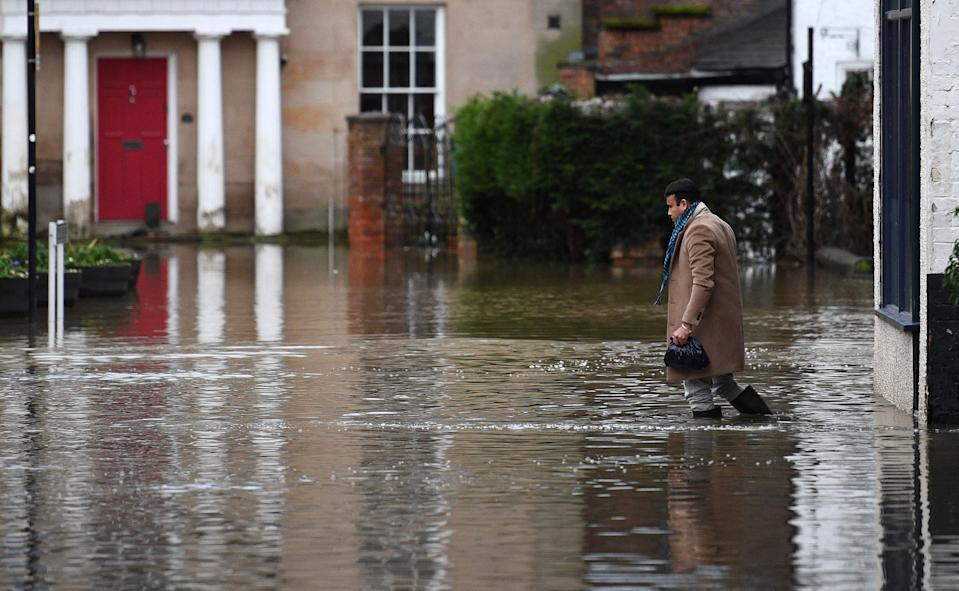 A man wades through flood water in Shrewsbury, western England after Storm Christoph brought heavy rains and flooding across the country AFP via Getty Images