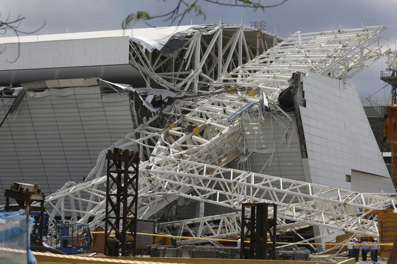 """Workers stand next to a crane that collapsed on the site of the Arena Sao Paulo stadium, known as """"Itaquerao"""", which will host the opening soccer match of the 2014 World Cup, in Sao Paulo November 27, 2013. A crane collapsed on Wednesday at the construction site of a future World Cup soccer stadium in Sao Paulo, Brazil, killing at least three people and causing damage to the structure, local media said. REUTERS/Nacho Doce (BRAZIL - Tags: SPORT SOCCER WORLD CUP)"""