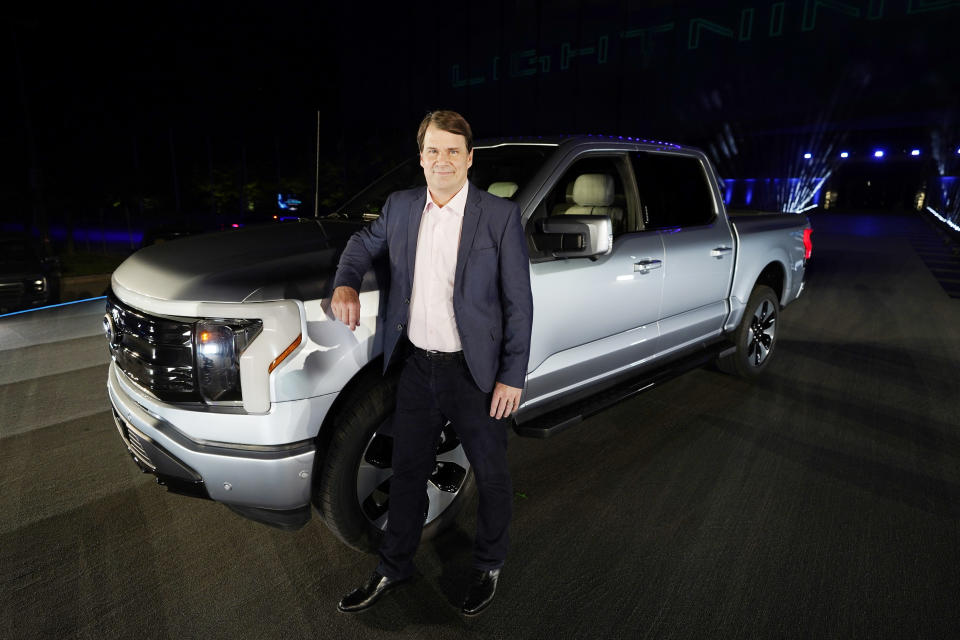 Jim Farley, Ford Motor Company's chief executive officer, stands next to the company's new Ford F-150 Lightning, Wednesday, May 19, 2021, in Dearborn, Mich. On the outside, the electric version of Ford's F-150 pickup looks about the same as the wildly popular gas-powered truck. The new truck called the F-150 Lightning can go up to 300 miles per charge, with a starting price of just under $40,000. (AP Photo/Carlos Osorio)