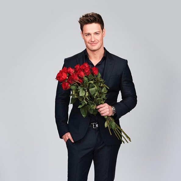 The Bachelor Australia 2019 Matt Agnew holds a bouquet of roses dressed in a suit