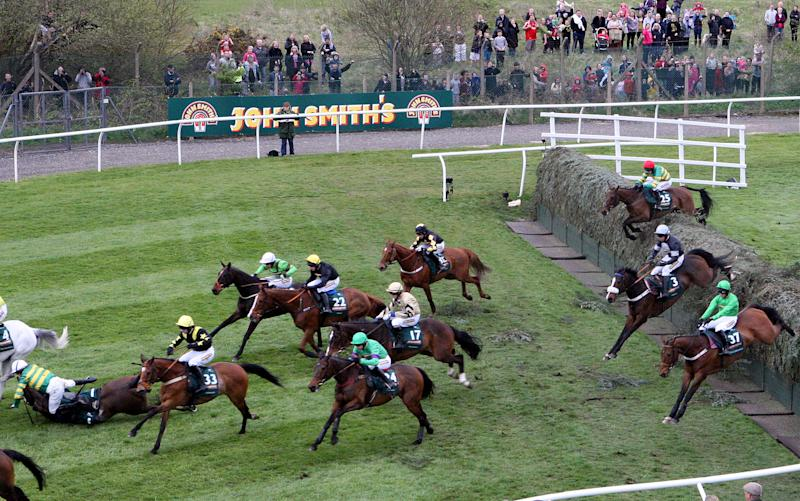 Synnchronized riden by Tony McCoy, left, falls after jumping Becher's Brook during the Grand National at Aintree Racecourse, Liverpool, England, Saturday April 14, 2012. Pre-race favorite Synchronised died Saturday after collapsing during the world's toughest steeplechase, which was won by Neptune Collonges in one of the race's closest finishes. (AP Photo/Scott Heppell)