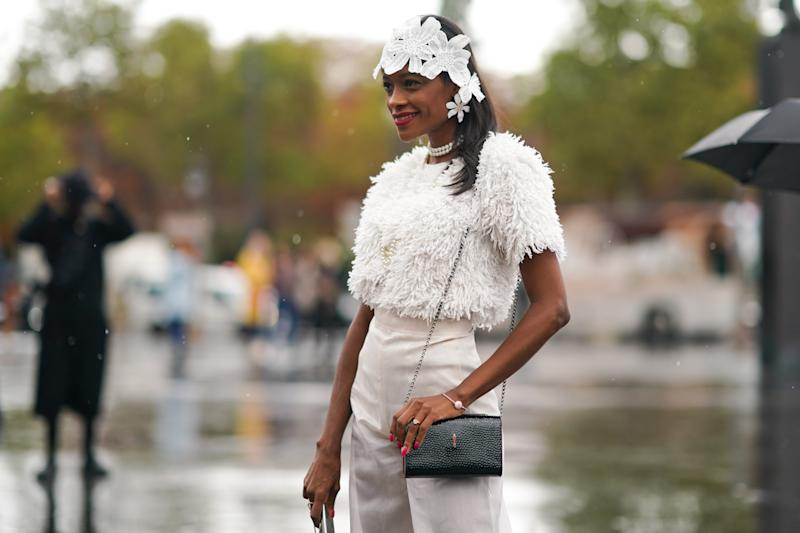 PARIS, FRANCE - OCTOBER 01: A guest wears a white lace headband, earrings, pearl necklaces, a white fluffy short sleeves top, white pants, a shiny black bag, outside Chanel, during Paris Fashion Week - Womenswear Spring Summer 2020, on October 01, 2019 in Paris, France. (Photo by Edward Berthelot/Getty Images)