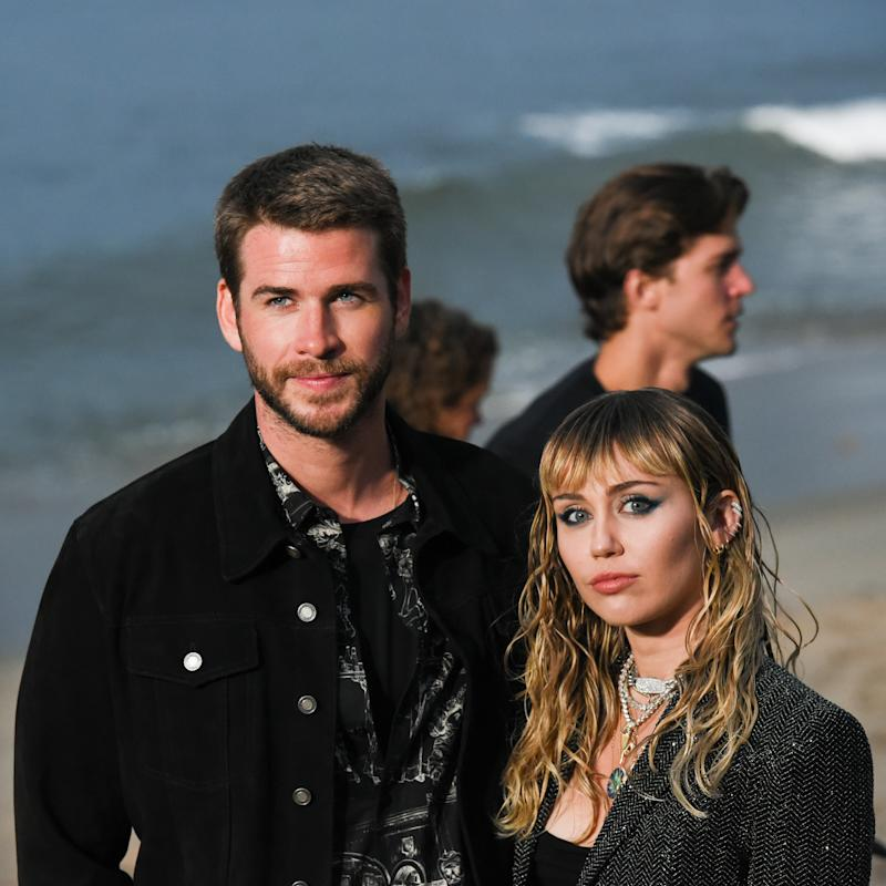Liam Hemsworth and Miley Cyrus at Saint Laurent mens spring summer 20 show on June 06, 2019 in Malibu, California. (Photo by Presley Ann/WireImage,)