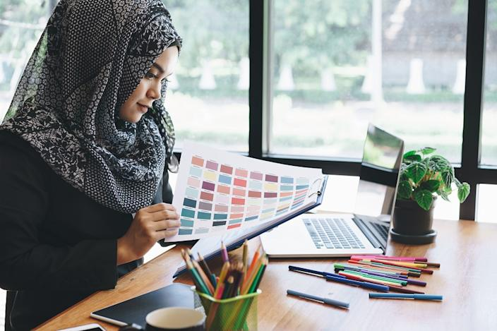 Beautiful young muslim creative designer woman using color palette samples and laptop in office.
