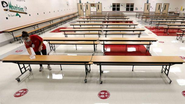 PHOTO: A Garland Independent School District custodian wipes down tables in the cafeteria at Stephens Elementary School in Rowlett, Texas, Wednesday, July 22, 2020. (Lm Otero/AP)
