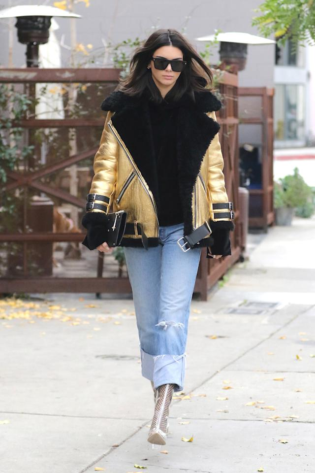 <p>Kendall Jenner is known for her incredible street style, and her outfit during a recent shopping trip in Los Angeles, Calif., did not disappoint. The model wore a $3,000 black and gold Acne Studios Velocite Jacket with a House of Sunny velour hoodie, Re/Done Levi's jeans, a black Dylan Kain clutch, and Ego perspex clear ankle boots. (Photo: Elite Images / AKM-GSI') </p>