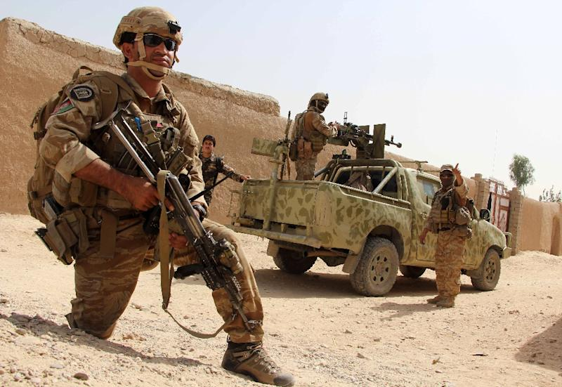 Afghan commandos take position during a military operation in Helmand province on October 2, 2016