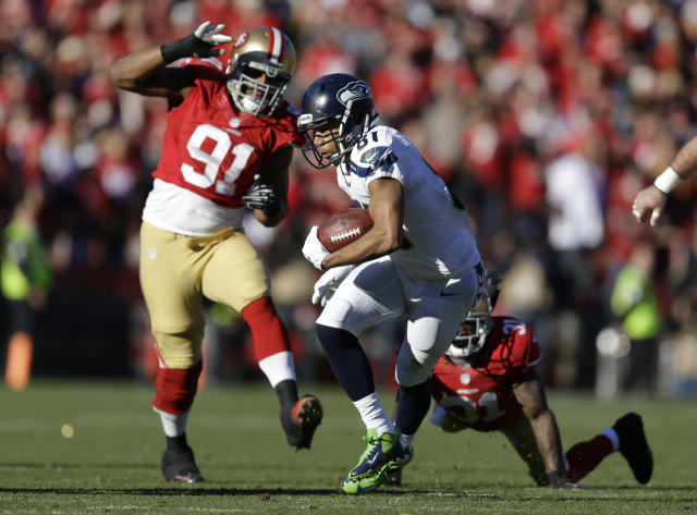 Seattle Seahawks wide receiver Golden Tate, center, carries the ball past San Francisco 49ers defensive end Ray McDonald, left, and San Francisco 49ers strong safety Donte Whitner, right, in the first half of an NFL football game, Sunday, Dec. 8, 2013, in San Francisco. (AP Photo/Ben Margot)