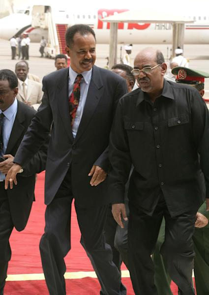 FILE - In this Tuesday, June 12, 2006 file photo, Sudanese president Omar al-Bashir, right, greets his Eritrean counterpart Isaias Afworki, left, as he arrives at the airport for a one-day visit in Khartoum, Sudan. More than 100 dissident soldiers stormed the Ministry of Information in the small East African nation of Eritrea on Monday, Jan. 21, 2013 and read a statement on state TV saying the country's 1997 constitution would be put into force, two Eritrea experts said. (AP Photo/Abd Raouf, File)