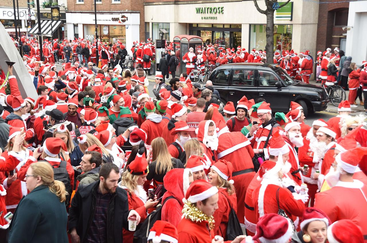 <p>A London black cab is surrounded by Santas as revellers take to the streets of London. (Rex) </p>