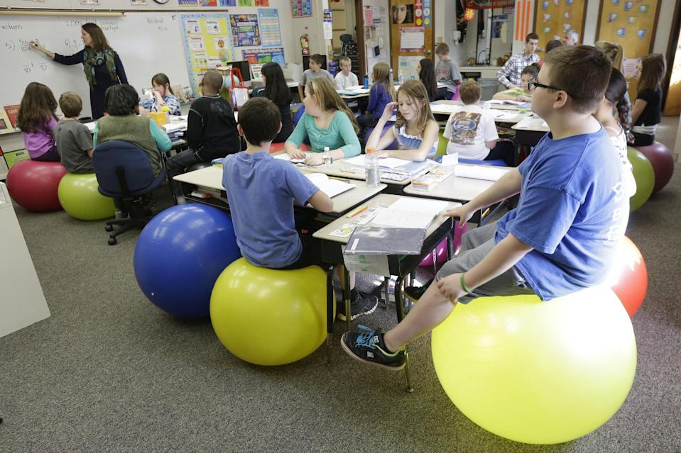Robbi Giuliano teaches her fifth grade class as they sit on yoga balls at Westtown-Thornbury Elementary School Monday, Feb. 4, 2013, in West Chester, Pa. Replacing stationary seats with inflatable bouncers has raised productivity in her fifth-graders at Westtown-Thornbury Elementary School, making students better able to focus on lessons while improving their balance and core strength, she said. (AP Photo/Matt Rourke)