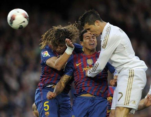 Barcelona's Carles Puyol (L) and Thiago Alcantara (C) jump for the ball against Real Madrid's Cristiano Ronaldo