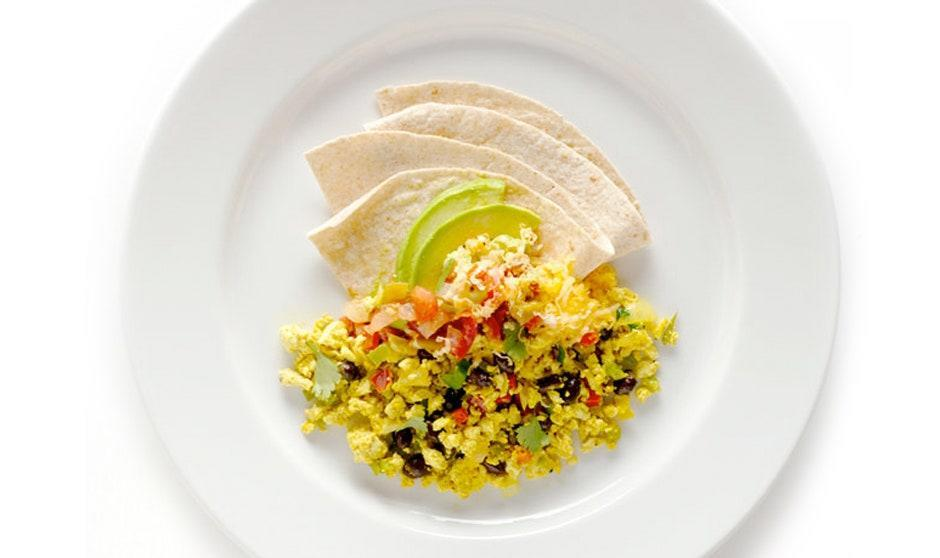 """There's cooking magic at work here: The turmeric turns the tofu yolk-yellow, and the garnishes lend the whole dish a huevos rancheros vibe. <a href=""""https://www.bonappetit.com/recipe/tofu-scramble?mbid=synd_yahoo_rss"""" rel=""""nofollow noopener"""" target=""""_blank"""" data-ylk=""""slk:See recipe."""" class=""""link rapid-noclick-resp"""">See recipe.</a>"""