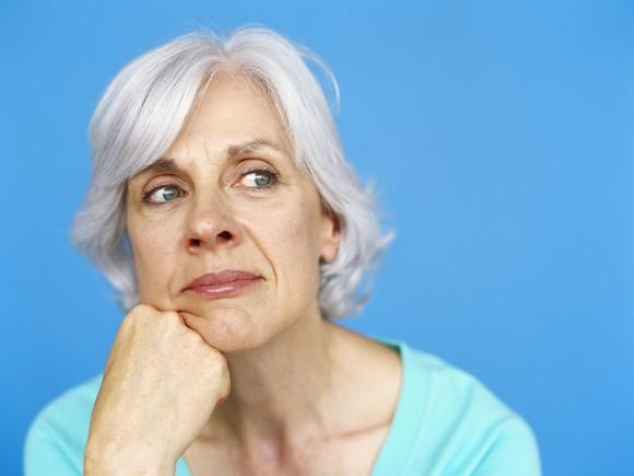 Mature woman thinking with chin on fist against blue background
