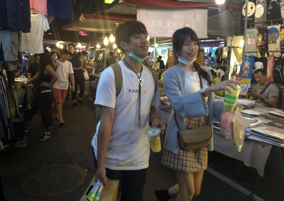 People wear face masks to protect against the spread of the coronavirus and visit at a night market in Taipei, Taiwan, Friday, Sept. 25, 2020. (AP Photo/Chiang Ying-ying)