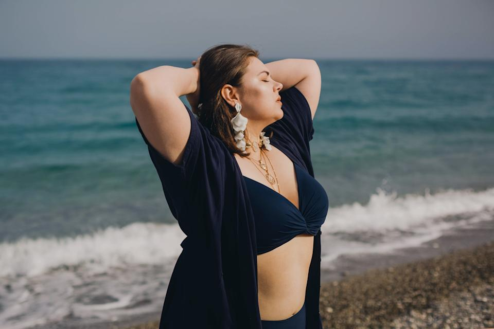 Attractive busty curvy woman in a blue swimsuit resting on the beach. Stylish accessories, fringe, fashion for plus size, beautuful sea. Bodypositive, natural authentic beauty, resort, summer vacation. Copy space.