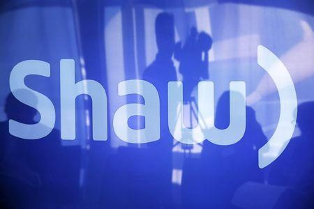 A television cameraman is reflected on a television screen displaying the Shaw logo during the Shaw AGM in Calgary