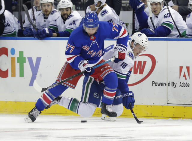 New York Rangers' Tony DeAngelo (77) and Vancouver Canucks' Jake Virtanen (18) fights for control of the puck during the first period of an NHL hockey game Monday, Nov. 12, 2018, in New York. (AP Photo/Frank Franklin II)