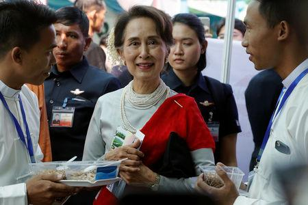 Myanmar's State Counsellor Aung San Suu Kyi tastes locally made dry fish during the Rakhine State Investment Fair at Ngapali beach in Thandwe