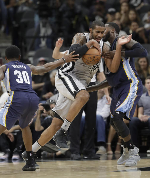 San Antonio Spurs forward LaMarcus Aldridge (12) drives between Memphis Grizzlies defenders Troy Daniels (30) and JaMychal Green (0) during Game 1 of a first-round NBA basketball playoff series, Saturday, April 15, 2017, in San Antonio. (AP Photo/Eric Gay)