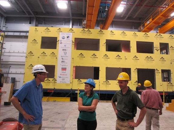 Benjamin Schafer (left), Kara Peterman (center) and structural engineer Rob Madsen (right, in the green shirt) stand in front of their cold-formed steel building and discuss the results of the structure's earthquake test.