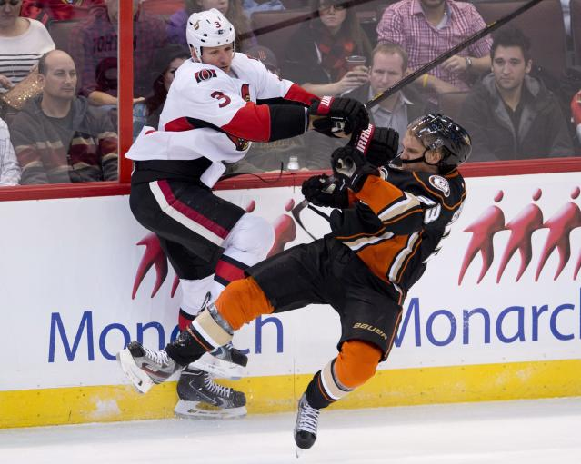 Ottawa Senators defenseman Marc Methot collides with Anaheim Ducks left wing Jakob Silfverberg along the boards during the second period of an NHL hokey game, Friday Oct. 25, 2013 in Ottawa, Ontario. (AP Photo/The Canadian Press, Adrian Wyld)
