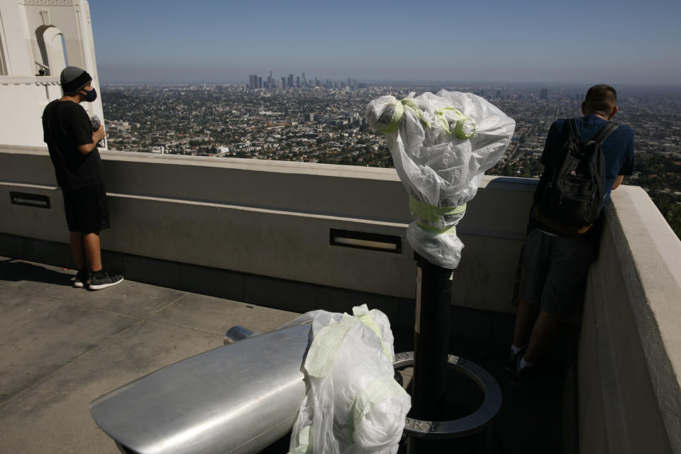 """Two people stand near telescopes wrapped in plastic to prevent the spread of COVID-19 at the Griffith Observatory overlooking downtown Los Angeles, Wednesday, July 15, 2020. Coronavirus cases have surged to record levels in the Los Angeles area, putting the nation's largest county in """"an alarming and dangerous phase"""" that if not reversed could overwhelm intensive care units and usher in more sweeping closures, health officials said Wednesday. (AP Photo/Jae C. Hong)"""