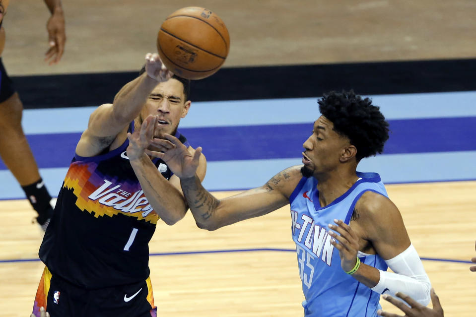 Phoenix Suns guard Devin Booker (1) is fouled by Houston Rockets center Christian Wood (35) while passing the ball during the second half of an NBA basketball game Wednesday, Jan. 20, 2021, in Houston. (AP Photo/Michael Wyke)