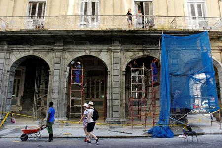 Tourists walk next to building being renovated, in Havana, Cuba July 21, 2018. REUTERS/Stringer