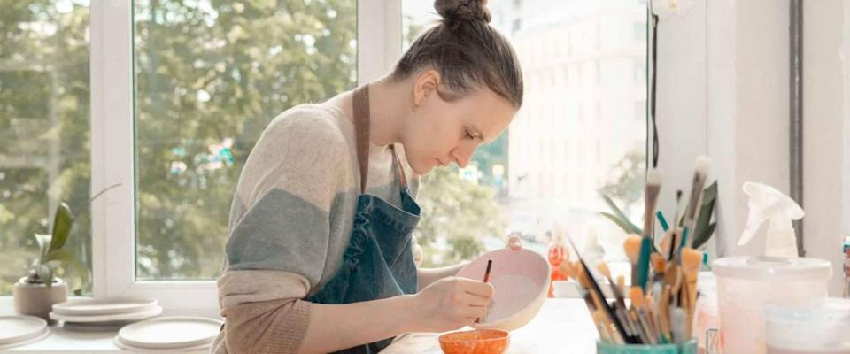 Young woman in an apron sitting at the table and leaning on a ceramic bowl.
