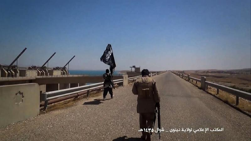 An image taken from a video released by Welayat Nineveh Media Office on August 9, 2014, allegedly shows Islamic State militants waving the trademark Jihadits flag as they inspect the grounds of the Mosul dam in Iraq (AFP Photo/)