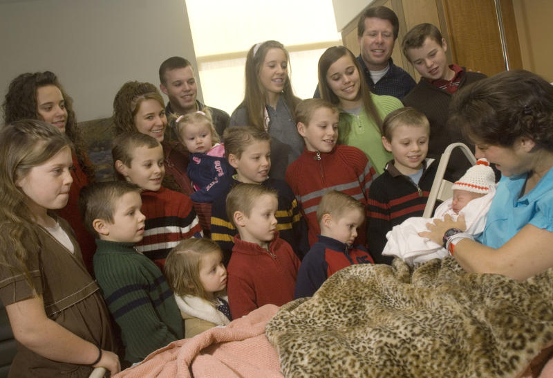 "Michelle Duggar holds her newborn daughter, Jordyn-Grace Makiya Duggar, as 16 of her other children and husband Jim Bob, second from the top right, watch on Friday, Dec. 19, 2008 in Rogers, Ark. Jordyn-Grace was born on Dec. 18, 2008, and weighed 7 lbs. 3 oz. and was 20 inches long. The cable network TLC broadcasts a weekly show about the Duggars, called ""17 Kids and Counting."" (AP Photo/Beth Hall)"