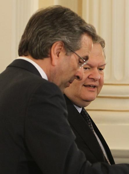 Greece's Prime Minister Antonis Samaras, left, and Socialist party head Evangelos Venizelos, who was named deputy prime minister and foreign minister converse after a swearing in ceremony at the Presidential palace in Athens, Tuesday, June 25, 2013. Greece's new cabinet was sworn in Tuesday after a broad reshuffle in which conservative Prime Minister Antonis Samaras handed key posts to the coalition government's minority Socialist party following a political crisis. (AP Photo/Thanassis Stavrakis)