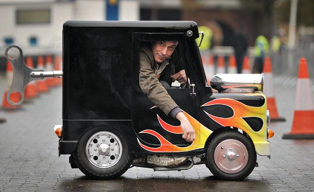 British inventor of the world's smallest legally roadworthy car Perry Watkins sits in his vehicle measuring 104.14cm high, 66.04cm wide and 132.08cm long at Guinness World Records Day in London on November 17, 2011. Wacky Guinness world record holders got together to race their unlikely vehicles like the world's fastest toilet and smallest roadworthy car in London the mark the 7th annual Guinness World Records day.  AFP PHOTO / BEN STANSALL