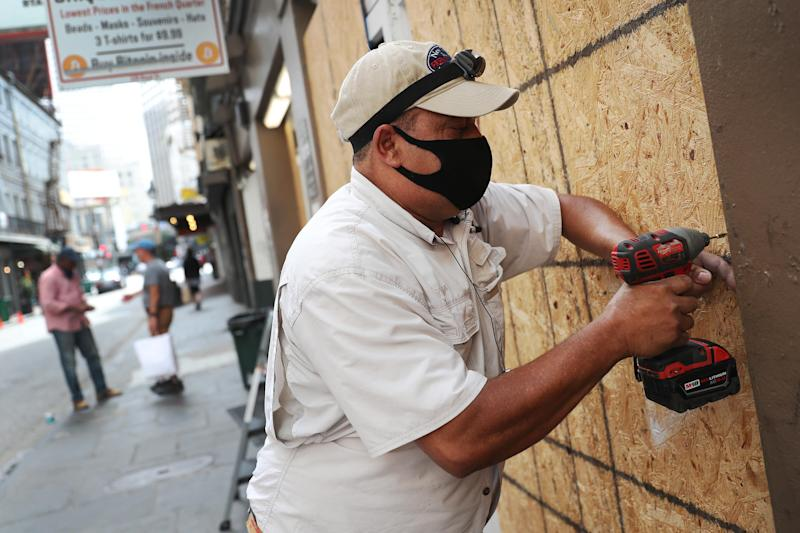 Luis A. Sanabria puts plywood over the windows of a business in the historic French Quarter on Monday, September 14, 2020, in New Orleans. / Credit: Joe Raedle / Getty