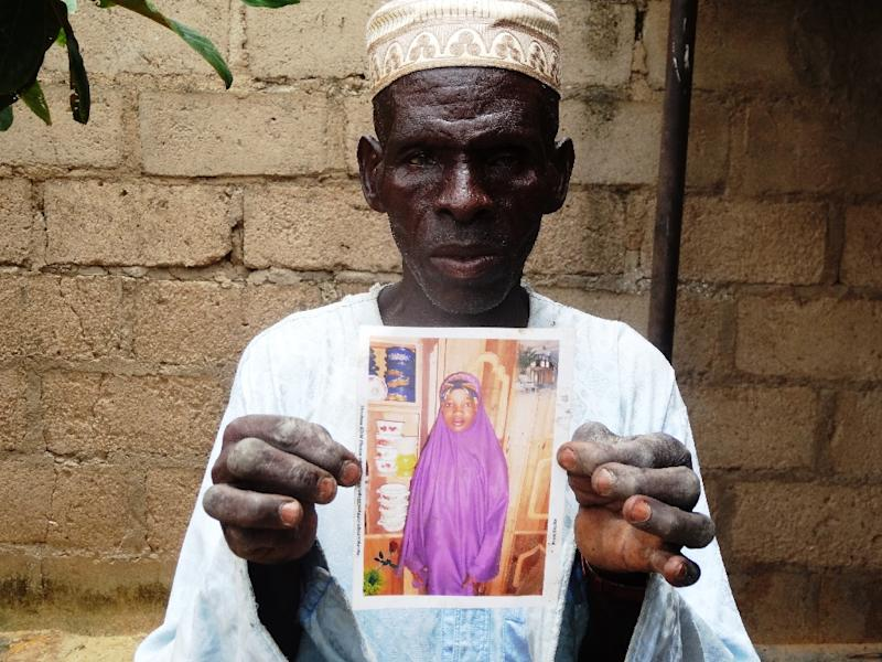 Sani Garba holds a picture of his daughter-in-law Wasila Tasi'u on August 10, 2014 inside her abandoned matrimonial home in the village of Unguwar Yansoro, outside Kano (AFP Photo/Aminu Abubakar)