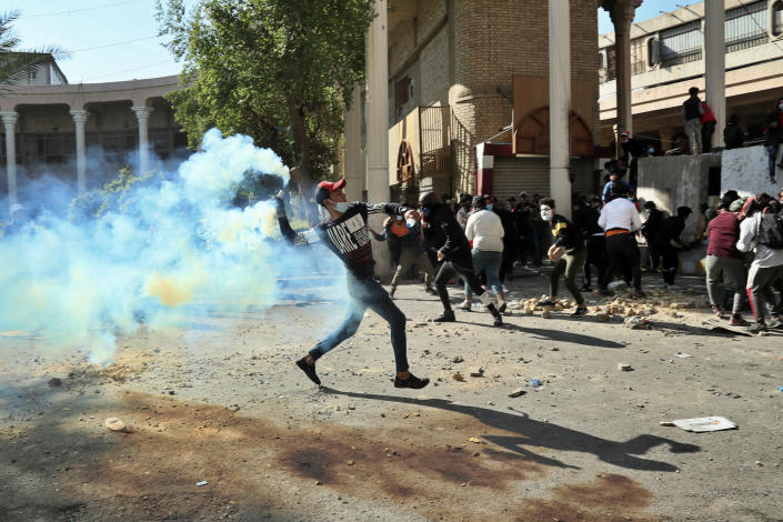 An anti-government protester throws throw back a tear gas canister fired by police during clashes in Baghdad, Iraq, Nov. 22, 2019. (Photo: Hadi Mizban/AP)