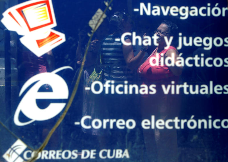 In this May 11, 2012 photo, people are reflected in an advertisement for Internet, chat and e-mail at a state-run computer center in Havana, Cuba. Cuban officials welcomed the arrival of an undersea fiber-optic cable linking the country to Venezuela, which was supposed to boost web capacity 3,000-fold. Even a retired Fidel Castro had hailed the dawn of a new cyber-age on the island. More than a year later, the government barely speaks of the cable anymore and Cuba's internet connection is still the slowest in the hemisphere. (AP Photo/Franklin Reyes)