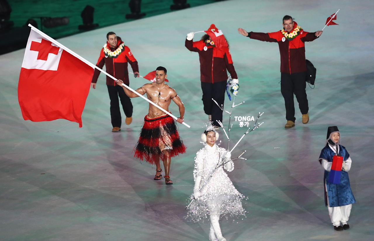 <p>Flag bearer Pita Taufatofua of Tonga leads the team — shirtless — while his teammates wear red zip jackets and black pants during the opening ceremony of the 2018 PyeongChang Games. (Photo: Ronald Martinez/Getty Images) </p>