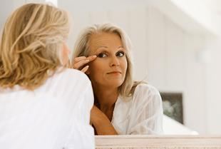 woman looking at crow's feet in the mirror