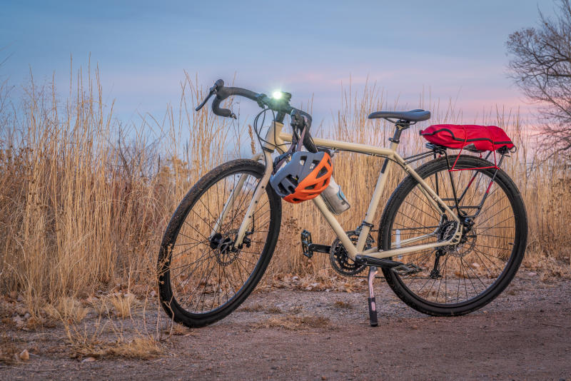 touring bicycle at dusk with headlight on in late fall or winter scenery in northern Colorado - a gravel trail in Riverbend Ponds Natural Area in Fort Collins