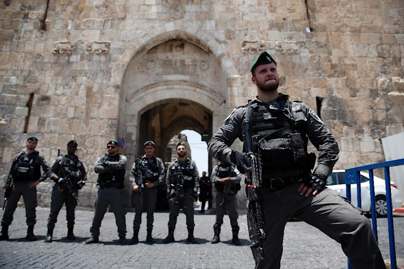 Israeli security forces stand guard as Palestinians worshippers demonstrate outside the Lions Gate, a main entrance to the Al-Aqsa mosque compound, due to new security measures by Israeli authorities, in Jerusalem's Old City on July 17, 2017 (AFP Photo/AHMAD GHARABLI)