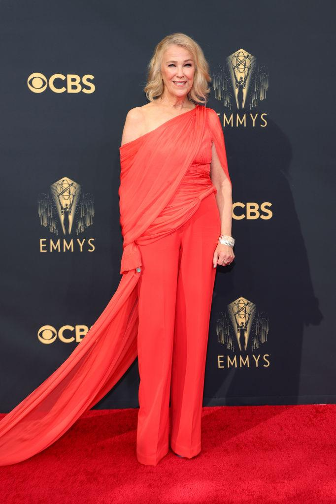 """<p>The Emmy award-winning """"Schitt's Creek"""" actress chose a coral suit and off-the-shoulder top with flowing train by Cong Tri.<em> (Image via Getty Images)</em></p>"""