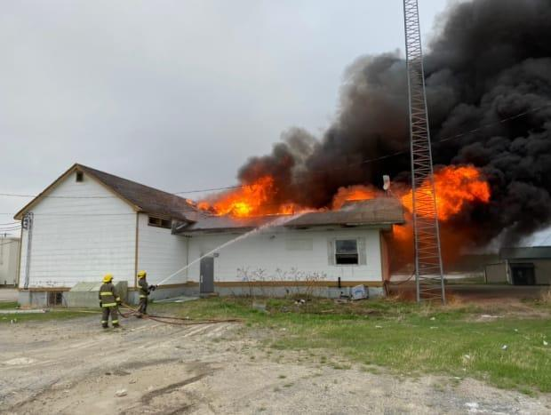 A building in Cross Lake, Man., caught fire early Thursday morning. Firefighters are shown here working to extinguish it. (Submitted by Manitoba RCMP - image credit)