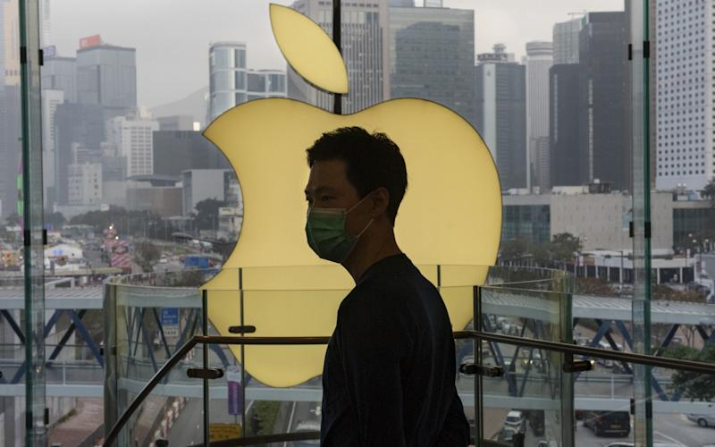 An employee stands in front of an Apple store logo in Hong Kong, where the company has been accused of assisting the Chinese government - Budrul Chukrut/Getty/Barcroft